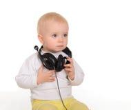 Παιχνίδι μωρών με τα ακουστικά στην άσπρη ανασκόπηση στοκ φωτογραφία