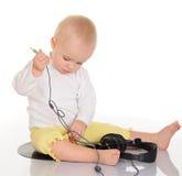 Παιχνίδι μωρών με τα ακουστικά στην άσπρη ανασκόπηση Στοκ εικόνα με δικαίωμα ελεύθερης χρήσης
