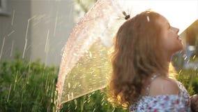 Παιχνίδι νέων κοριτσιών στη βροχή με την ομπρέλα Παιδί Cutie που έχει τη διασκέδαση υπαίθρια φιλμ μικρού μήκους