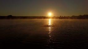 Παιχνίδι νεαρών άνδρων με το νερό στο ηλιοβασίλεμα στη λίμνη απόθεμα βίντεο