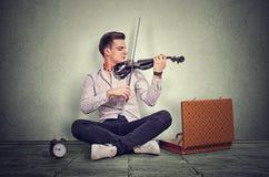 Παιχνίδι νεαρών άνδρων σε ένα μαύρο ηλεκτρονικό βιολί στοκ φωτογραφία με δικαίωμα ελεύθερης χρήσης