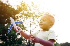 Παιχνίδι παιδάκι με το παιχνίδι αεροπλάνων στο πράσινο πάρκο Στοκ Εικόνες