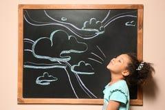 Παιχνίδι παιδιών αφροαμερικάνων στον πίνακα με συρμένο τον κιμωλία ουρανό στοκ φωτογραφίες