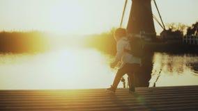 Παιχνίδι παιδιών με ένα ραβδί στην αποβάθρα λιμνών ηλιοβασιλέματος υποστηρίξτε την όψη εξερευνητής λίγα Καταπληκτικός ορίζοντας φ απόθεμα βίντεο