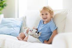 Παιχνίδι παιδιών με τη γάτα μωρών Παιδί και γατάκι στοκ εικόνες με δικαίωμα ελεύθερης χρήσης