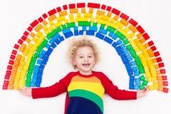 Παιχνίδι παιδιών με το πλαστικό παιχνίδι φραγμών ουράνιων τόξων Στοκ Φωτογραφίες