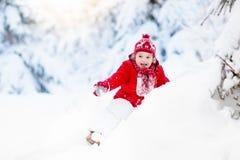Παιχνίδι παιδιών με το χιόνι το χειμώνα Αγόρι στο χιονώδες πάρκο Στοκ Εικόνες