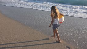 Παιχνίδι παιδιών στην παραλία στο ηλιοβασίλεμα, ευτυχές παιδί που περπατά στο κορίτσι κυμάτων θάλασσας στην παραλία απόθεμα βίντεο