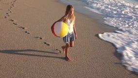 Παιχνίδι παιδιών στην παραλία στο ηλιοβασίλεμα, ευτυχές παιδί που περπατά στο κορίτσι κυμάτων θάλασσας στην παραλία φιλμ μικρού μήκους