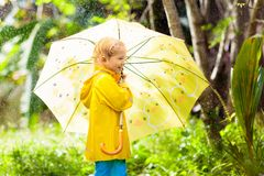 Παιχνίδι παιδιών στη βροχή Παιδί με την ομπρέλα στοκ εικόνα με δικαίωμα ελεύθερης χρήσης