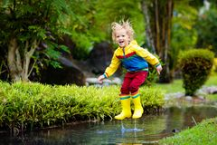 Παιχνίδι παιδιών στη λακκούβα Άλμα παιδιών στη βροχή φθινοπώρου στοκ εικόνα