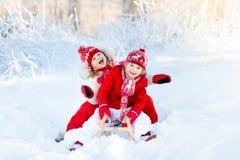 Παιχνίδι παιδιών στο χιόνι Γύρος χειμερινών ελκήθρων για τα παιδιά Στοκ Φωτογραφία