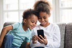 Παιχνίδι παιδιών χαμόγελου μικρό μαύρο με το smartphone από κοινού στοκ φωτογραφίες