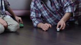 Παιχνίδι πατέρων και γιων με τα αυτοκίνητα παιχνιδιών στο πάτωμα στο σπίτι, έχοντας τη διασκέδαση από κοινού απόθεμα βίντεο
