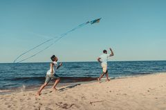 παιχνίδι πατέρων και γιων με τον ικτίνο στην παραλία στοκ εικόνα