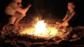 Παιχνίδι πατέρων και γιων στην παραλία κοντά στη φωτιά απόθεμα βίντεο