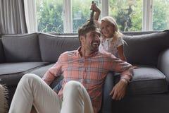 Παιχνίδι πατέρων και κορών μαζί στο καθιστικό στοκ εικόνα με δικαίωμα ελεύθερης χρήσης