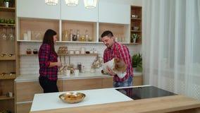 Παιχνίδι πατέρων με λίγες κόρη και μητέρα που προσέχουν τους στην κουζίνα απόθεμα βίντεο