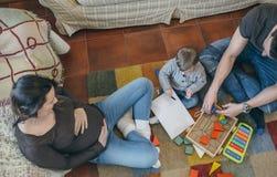 Παιχνίδι πατέρων με το μικρό παιδί ενώ η μητέρα εξετάζει τους στοκ εικόνες με δικαίωμα ελεύθερης χρήσης