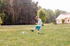 Παιχνίδι ποδοσφαίρου αγοριών με τη σφαίρα στο γήπεδο ποδοσφαίρου Στοκ Φωτογραφίες