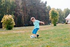 Παιχνίδι ποδοσφαίρου αγοριών με τη σφαίρα στο γήπεδο ποδοσφαίρου Στοκ εικόνες με δικαίωμα ελεύθερης χρήσης