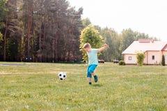 Παιχνίδι ποδοσφαίρου αγοριών με τη σφαίρα στο γήπεδο ποδοσφαίρου Στοκ φωτογραφίες με δικαίωμα ελεύθερης χρήσης
