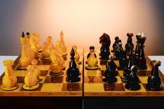 Παιχνίδι σκακιού με τα ηλέκτρινα κομμάτια σκακιού στον πίνακα στον άσ στοκ εικόνα