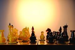 Παιχνίδι σκακιού με τα ηλέκτρινα κομμάτια σκακιού στον πίνακα Με το χρ στοκ εικόνα με δικαίωμα ελεύθερης χρήσης