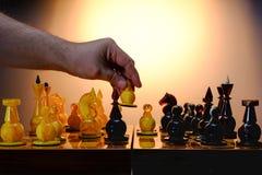 Παιχνίδι σκακιού με τα ηλέκτρινα κομμάτια σκακιού στον πίνακα Χέρι του φορέα που κρατά τον άσπρο αριθμό Με το χρυσό υπόβαθρο κλίσ στοκ φωτογραφία με δικαίωμα ελεύθερης χρήσης