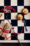 Παιχνίδι σκακιού με το χριστουγεννιάτικο δώρο και μπισκότα σε έναν ξύλινο τομέα Στοκ Φωτογραφίες