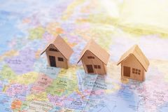 Παιχνίδι σπιτιών εγγράφου ή σπίτι χαρτονιού στον παγκόσμιο χάρτη με τον ήλιο πρωινού Στοκ Φωτογραφία