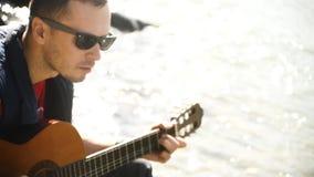 Παιχνίδι της κιθάρας στο υπόβαθρο του έντονου φωτός από το νερό φιλμ μικρού μήκους