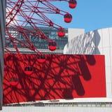 Παιχνίδι της σκιάς, του φωτός και του χρώματος μεταξύ της ρόδας ferris και των κτιρίων γραφείων στοκ εικόνες