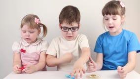 Παιχνίδι τριών ευτυχές παιδιών με τους κλώστες στον πίνακα απόθεμα βίντεο