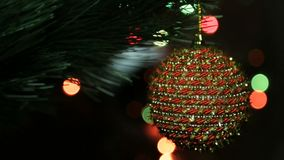 Παιχνίδι Χριστουγέννων σε ένα χριστουγεννιάτικο δέντρο ενάντια σε μια γιρλάντα στη θαμπάδα απόθεμα βίντεο