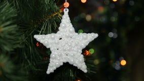 Παιχνίδι Χριστουγέννων σε ένα χριστουγεννιάτικο δέντρο ενάντια σε μια γιρλάντα στη θαμπάδα φιλμ μικρού μήκους
