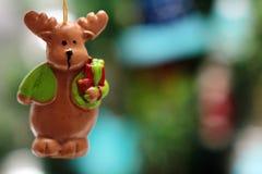 Παιχνίδι χριστουγεννιάτικων δέντρων, ελάφια Χριστουγέννων με το δώρο ενάντια στο χριστουγεννιάτικο δέντρο Εορταστική ανασκόπηση Χ Στοκ φωτογραφία με δικαίωμα ελεύθερης χρήσης