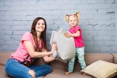 Παιχνίδι Mom και κορών στον καναπέ με την πάλη μαξιλαριών Ντυμένος στα φωτεινά μοντέρνα ενδύματα σε ένα δωμάτιο Στοκ Φωτογραφία