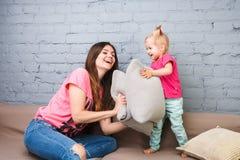 Παιχνίδι Mom και κορών στον καναπέ με την πάλη μαξιλαριών Ντυμένος στα φωτεινά μοντέρνα ενδύματα σε ένα δωμάτιο Στοκ φωτογραφίες με δικαίωμα ελεύθερης χρήσης