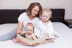 Παιχνίδι Mom με δύο παιδιά της στο σπίτι στοκ εικόνα
