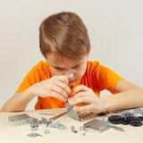 Παιχνίδια λίγων σοβαρά αγοριών με τη μηχανική εξάρτηση στον πίνακα Στοκ Εικόνες
