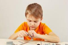 Παιχνίδια λίγων χαριτωμένα αγοριών με τη μηχανική εξάρτηση στον πίνακα Στοκ Εικόνα