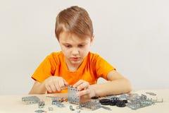 Παιχνίδια λίγων χαριτωμένα αγοριών με το μηχανικό κατασκευαστή στον πίνακα Στοκ Εικόνες