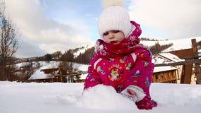 Παιχνίδια λίγων χαριτωμένα κοριτσιών με το χιόνι απόθεμα βίντεο