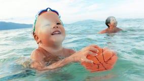 Παιχνίδια αγοριών και μητέρων με τη σφαίρα στη θάλασσα σε αργή κίνηση φιλμ μικρού μήκους
