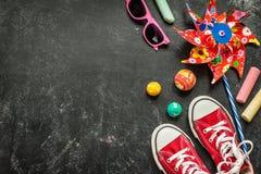 Παιχνίδια και κόκκινα πάνινα παπούτσια στο μαύρο πίνακα κιμωλίας - παιδική ηλικία Στοκ φωτογραφία με δικαίωμα ελεύθερης χρήσης