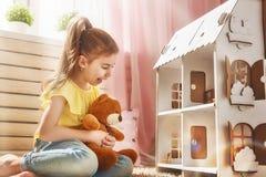 Παιχνίδια κοριτσιών με το σπίτι κουκλών Στοκ Εικόνες
