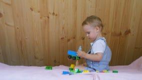 Παιχνίδια μικρά αγοράκι με τα παιχνίδια του στον καναπέ στο ηλιόλουστο δωμάτιο φιλμ μικρού μήκους