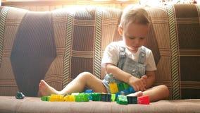 Παιχνίδια μικρά αγοράκι με τα παιχνίδια του στον καναπέ στο ηλιόλουστο δωμάτιο απόθεμα βίντεο