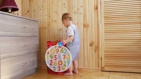 Παιχνίδια μικρά αγοράκι με τα παιχνίδια του στο ηλιόλουστο δωμάτιο φιλμ μικρού μήκους